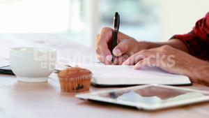 Hands of casual business man writing on paper