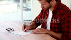 Casual business man writing on paper