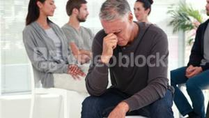 Man comforting another in rehab group at therapy