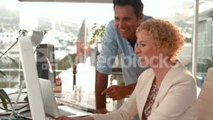 Casual business team working together with computer