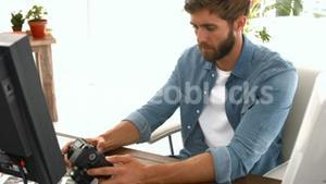 Photo editor looking at a digital camera
