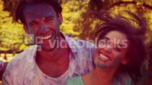 Happy friends covered with powder paint smiling at camera