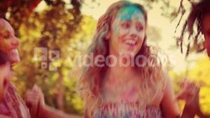 Happy friends covered with powder paint in the park