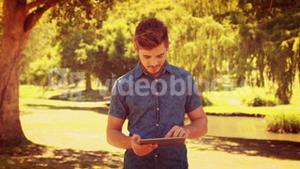 Handsome man using tablet in the park