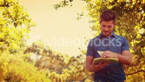 Handsome man reading a book in the park