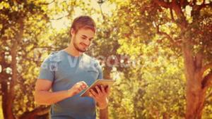 Handsome man using tablet and looking at camera in the park