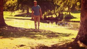 Handsome man walking in the park and holding retro photo camera