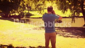Rear view of man walking and taking photo with retro camera