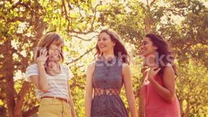 Happy female friends talking and laughing together in the park