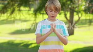 Little boy saying his prayers in the park