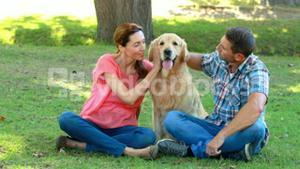 Happy couple with their dog in the park