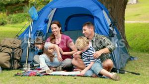 Happy family on a camping trip in front of their tent