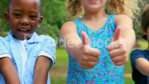 Happy children looking at camera with thumbs up