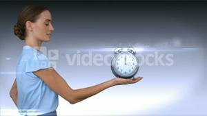 A businesswoman holding alarm clock