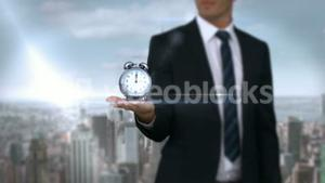 Businessman holding alarm clock