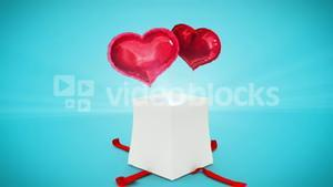 Digital animation of birthday gift exploding and revealing heart