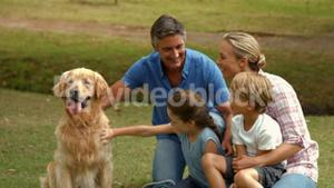 Happy family smiling at the camera with their dog