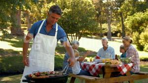 Happy man doing barbecue for his family and smiling at camera