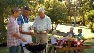 Happy man doing barbecue for his family