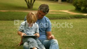 Happy father with his son using tablet in the park