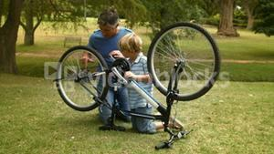 Father and his son fixing a bike in the park