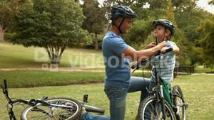 Father attaching his son cycling helmet in the park