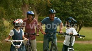 Happy family on their bike at the park smiling at camera