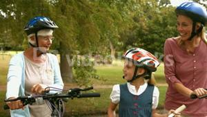 Happy multi generation family on their bike at the park