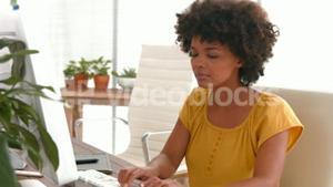 Happy casual businesswoman using computer