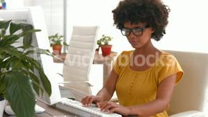 Serious casual businesswoman using computer