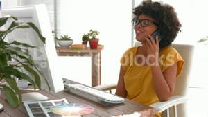 Happy casual businesswoman having a phone call and using computer