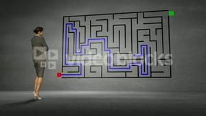 Businesswoman looking at grey wall with maze
