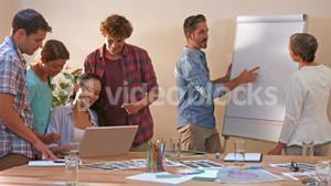 Creative business team working on laptop while their colleagues looking at white board