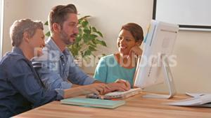Creative business team using computer and looking at camera