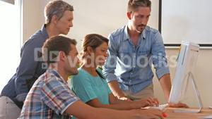 Creative business team looking at computer
