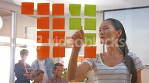 Casual businesswoman looking at post it with her colleagues behind