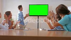 Creative team looking at television with green screen
