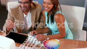 Casual designer looking at photo sample and color sample