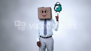 Businessman with a carton on the head pointing at an animated alarm clock