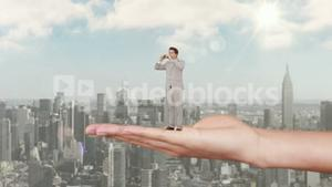 Hand holding standing businessman looking out above scyscrapers
