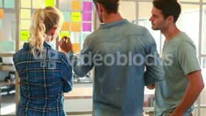 Casual business team looking at post it on the wall