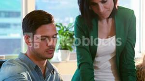 Casual business team using laptop during meeting