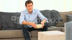 Young man watching a match on his tv