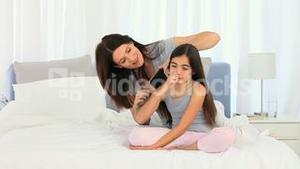 Mother fixing daughters hair