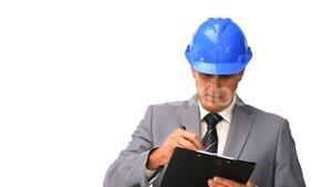 Businessman with safety helmet taking notes