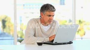 Casual middle aged man working on a laptop