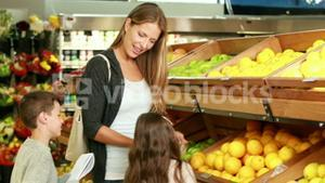 Mother and children picking out fruit in supermarket