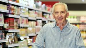 Senior man showing thumbs up at grocery store