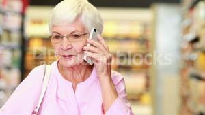 Senior woman on the phone in supermarket