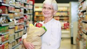 Senior woman with bag of veg in grocery store